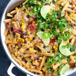 A white skillet filled with vegan taco pasta on a dark textured background.