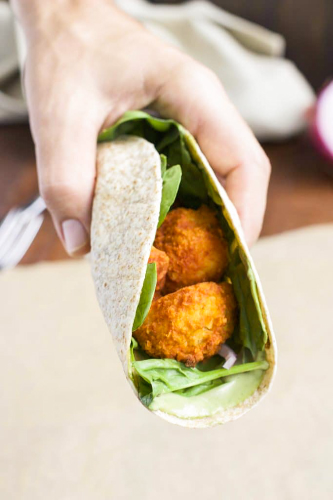 A hand holding a filled taco over a piece of parchment paper.