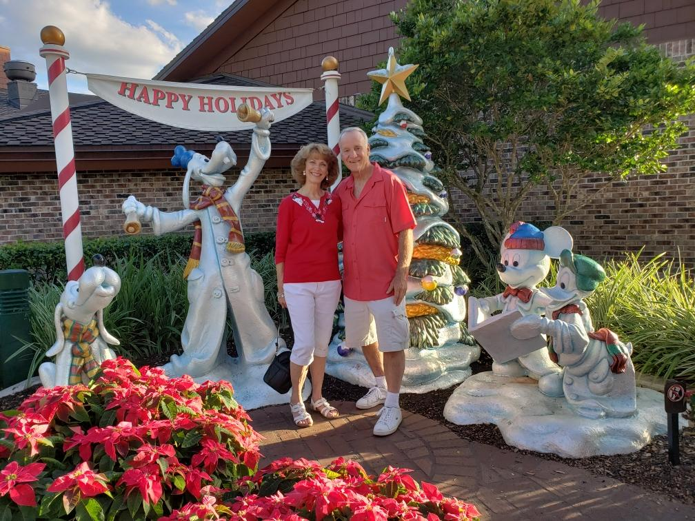 Free Christmas photo backdrop at Disney Springs with two people smiling.
