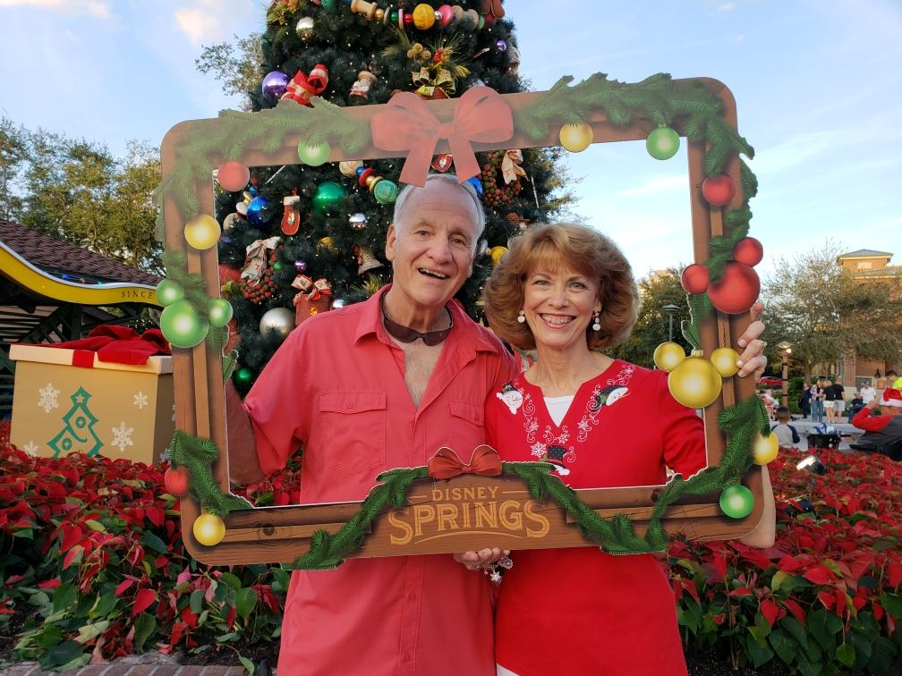 Two people smiling and holding a Disney Springs Christmas photo frame in from of them.