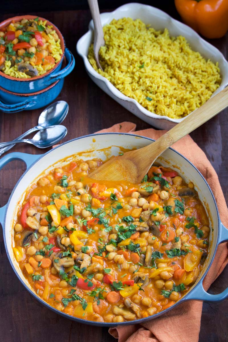 A large bowl of vegetable curry with a wooden spoon next to a few small bowls and a bowl of yellow rice.