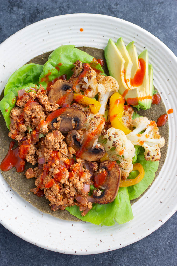 A low-carb taco filled with vegetables and tofu on a white plate.