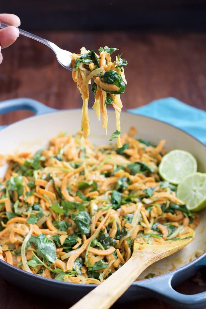 A hand holding a forkful of sweet potato noodles and spinach over a large blue pan on a rustic background.