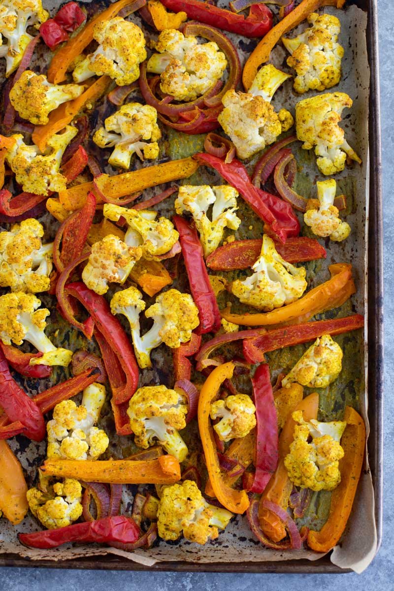 Roasted vegetables on a parchment-lined tray.