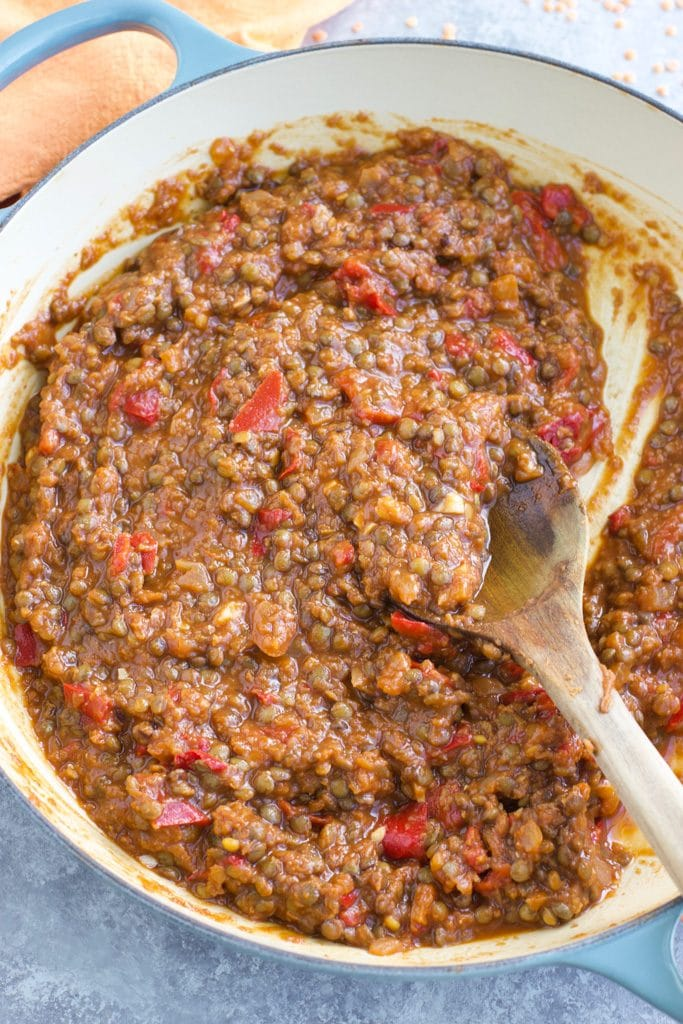 A large pan filled with vegan lentil sloppy Joe filling being stirred by a wooden spoon.