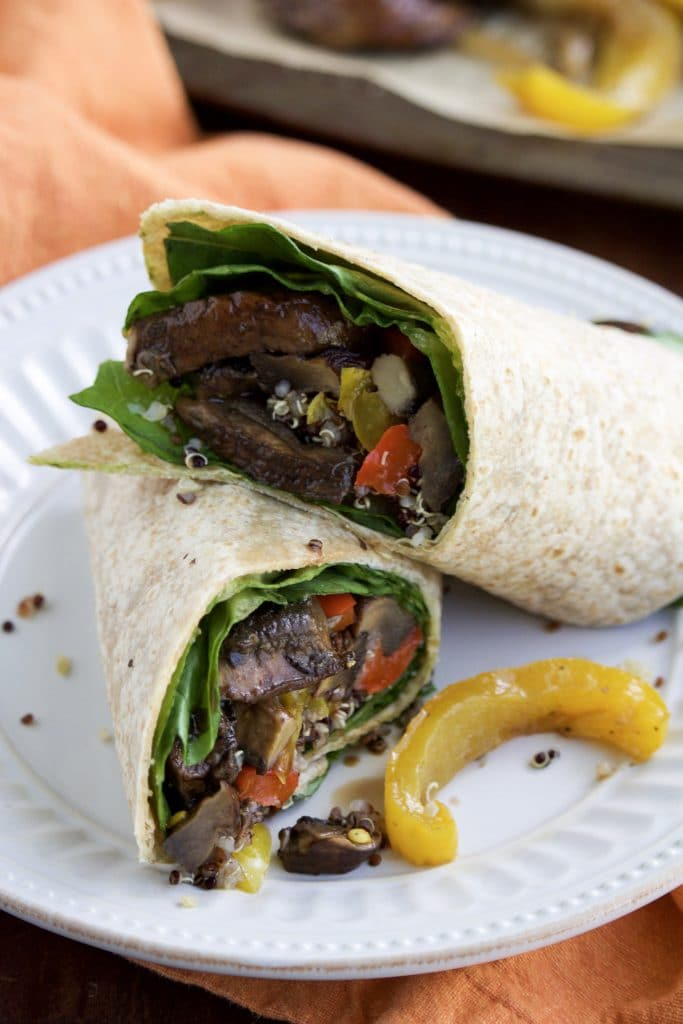 Close up view of a vegan wrap cut in half and stacked on top of each other on a white plate.