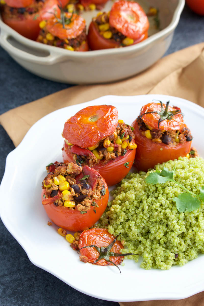 A white plate filled with stuffed tomatoes and a side of cilantro lime quinoa.