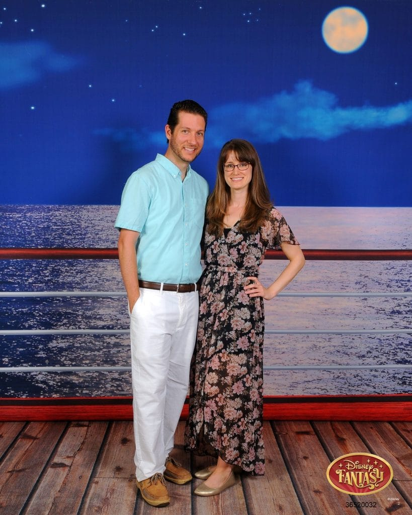 A man and woman smiling and posing in front of the railing at night on the Disney Fantasy.