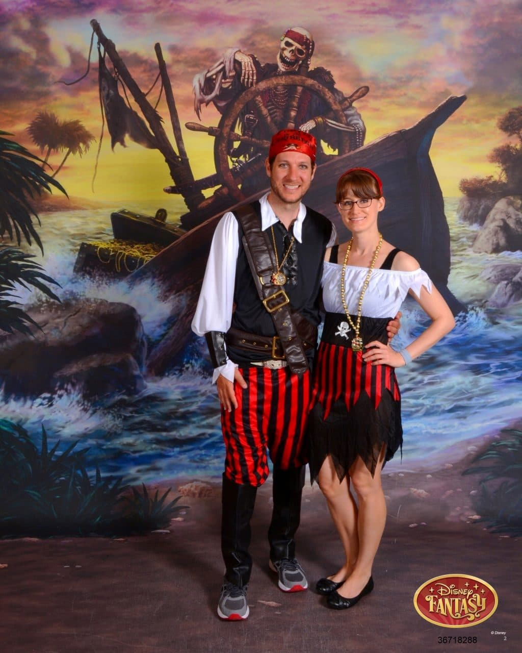 A man and woman dressed as pirates and smiling in front of a pirate ship on the Disney Fantasy.