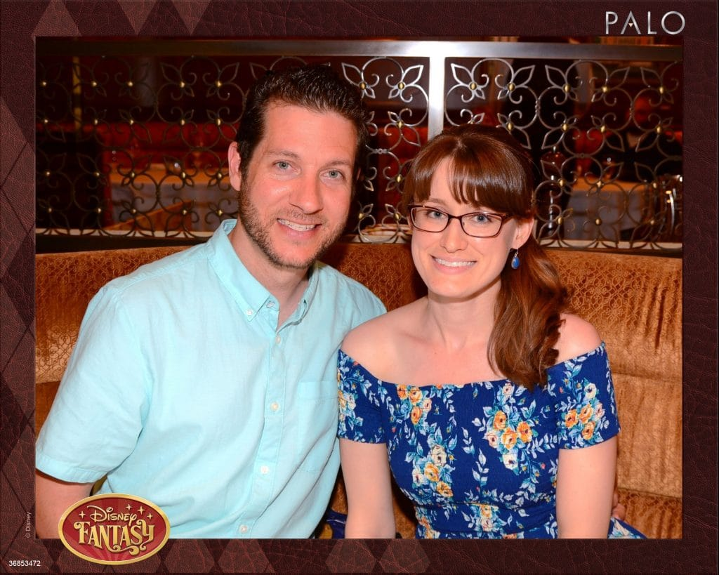 A man and woman smiling and sitting in a booth at Palo while eating dinner on the Disney Fantasy.