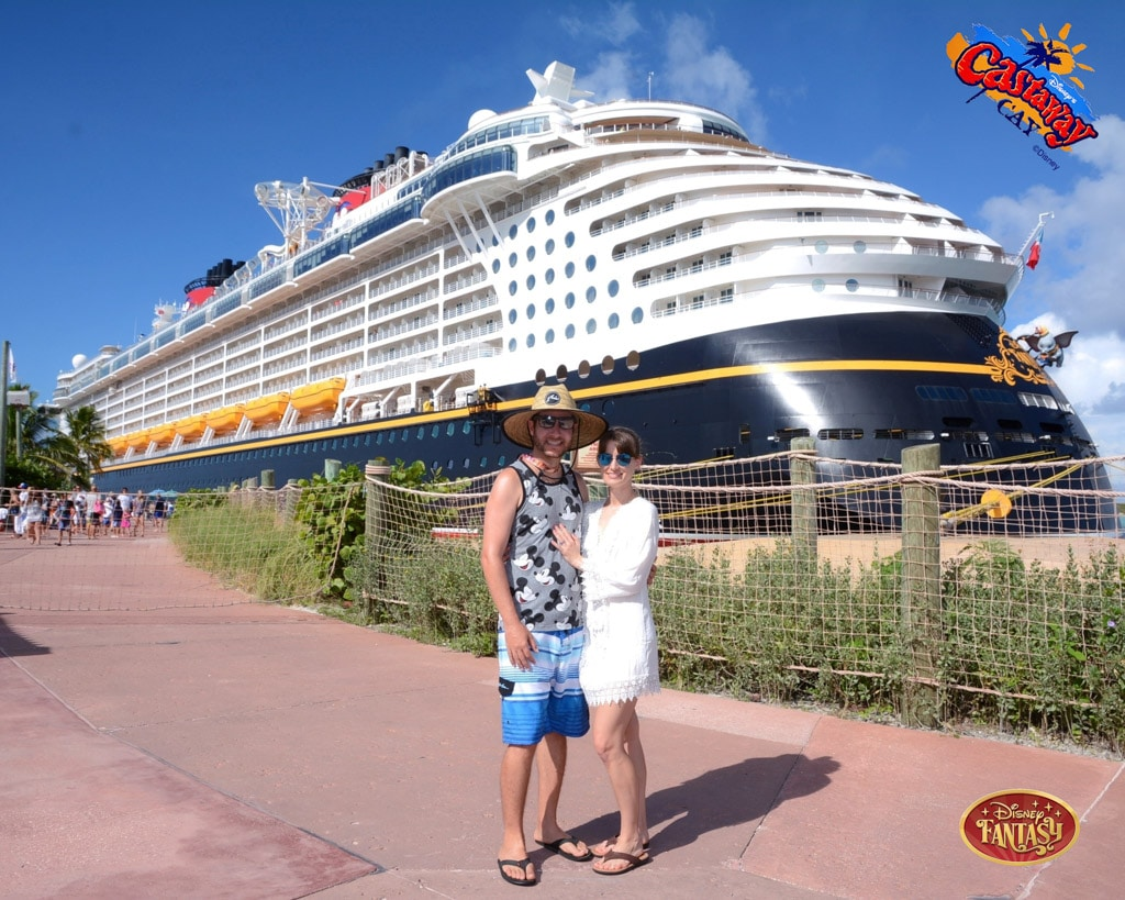 A happy couple posing in front of the Disney Fantasy ship while it's docked at Castaway Cay.