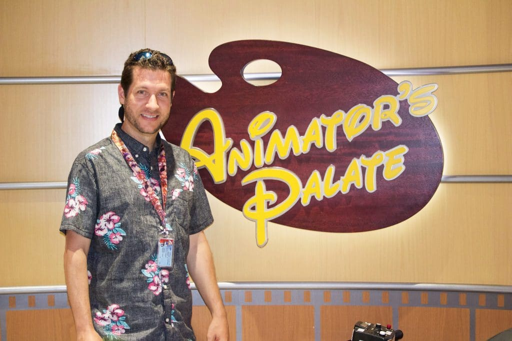 A man standing in front of the Animator's Palate sign on a Disney cruise.