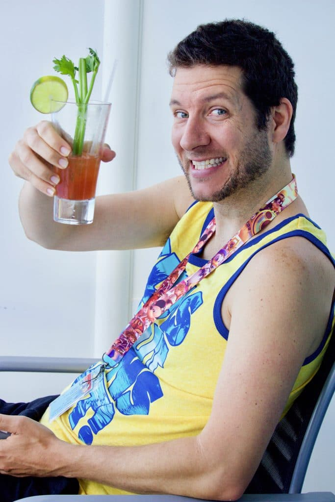A man in a yellow tank top holding a Bloody Mary.