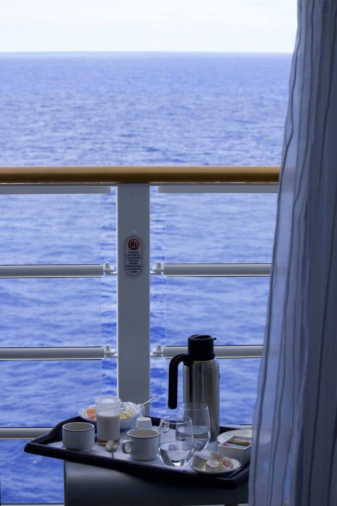 A room service tray filled with coffee, fruit, and water glasses on a verandah table on a Disney cruise.