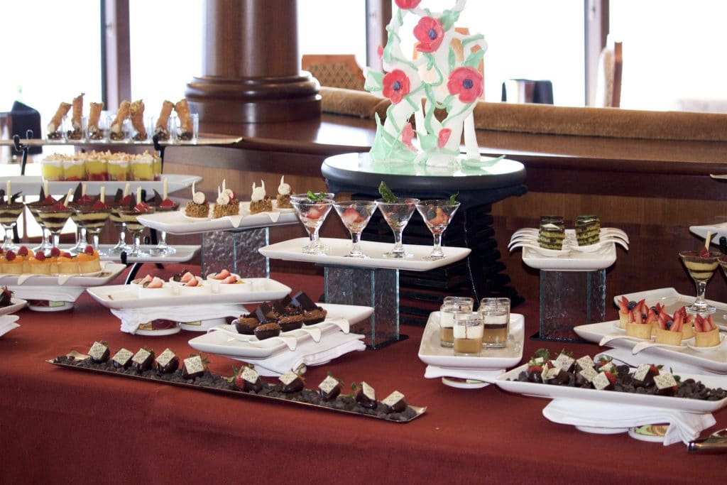 A table filled with multiple plate of small desserts at Palo on the Disney Fantasy.