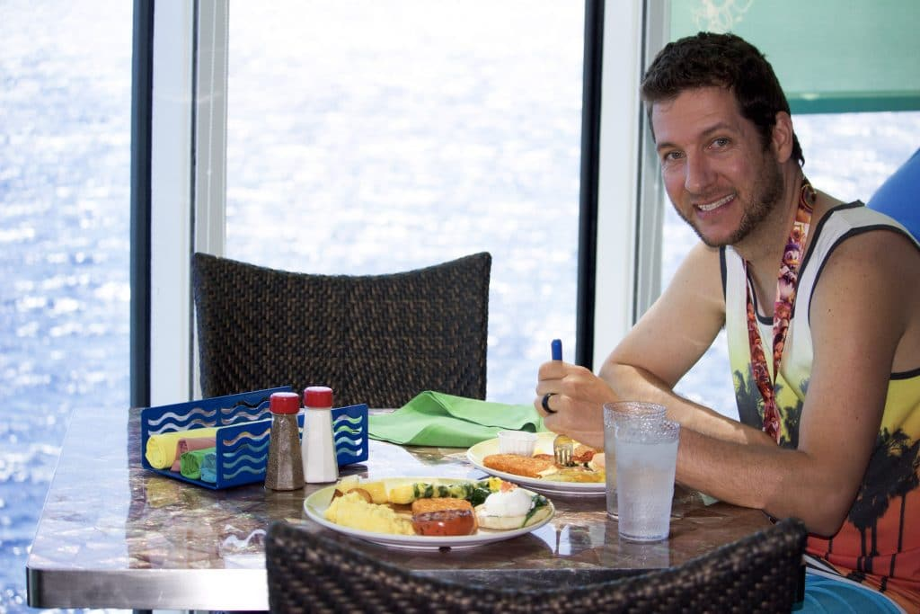 A man smiling and eating lunch at a table by a window overlooking the ocean on a Disney cruise.
