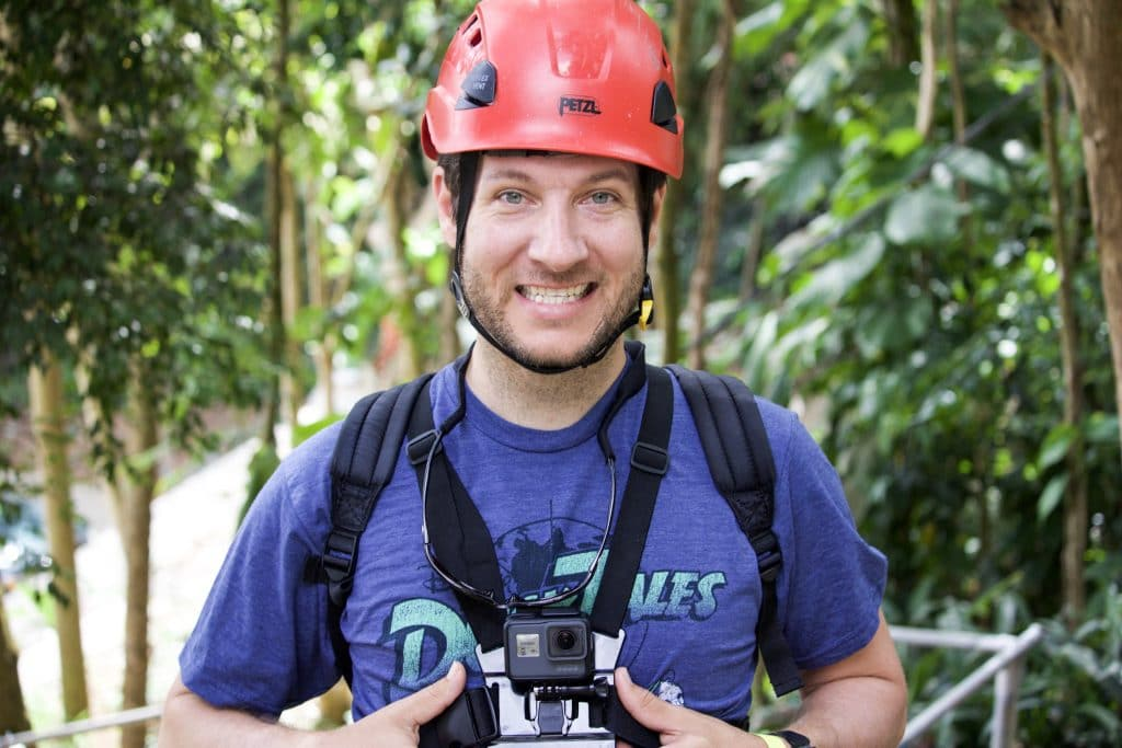 A young man smiling and wearing a red helmet and zipping gear.
