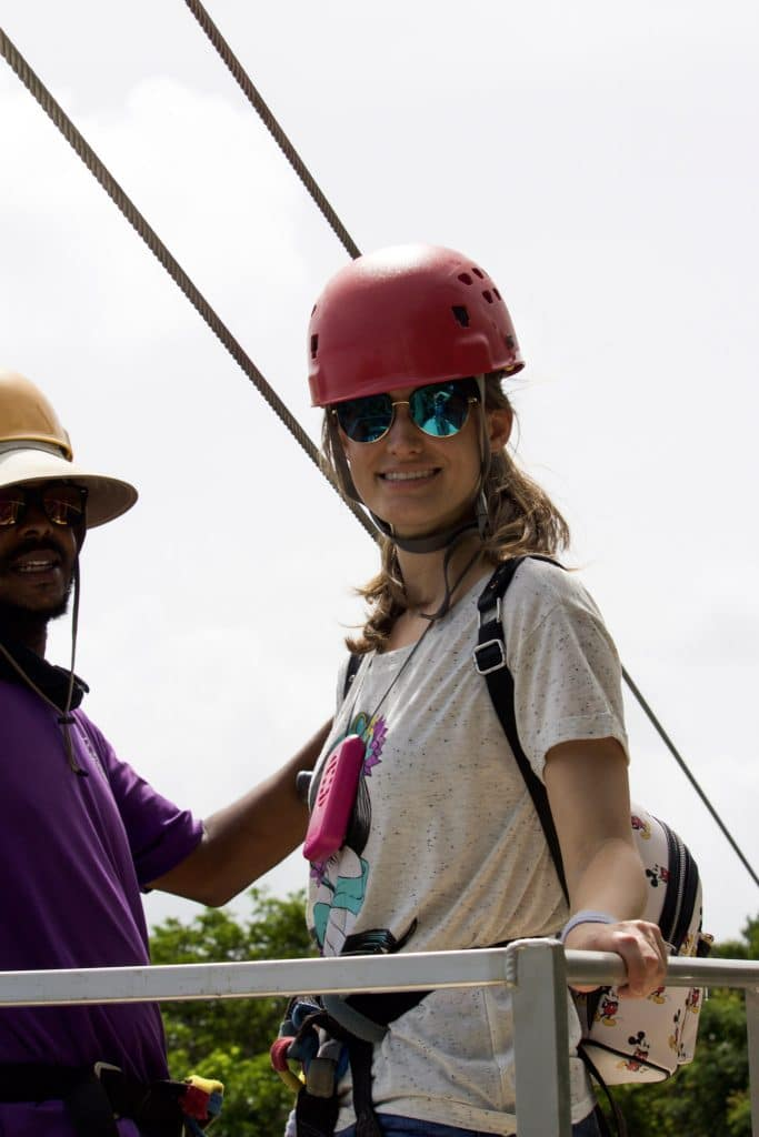 A young girl smiling while wearing a red helmet and be strapped into a zip lining harness.