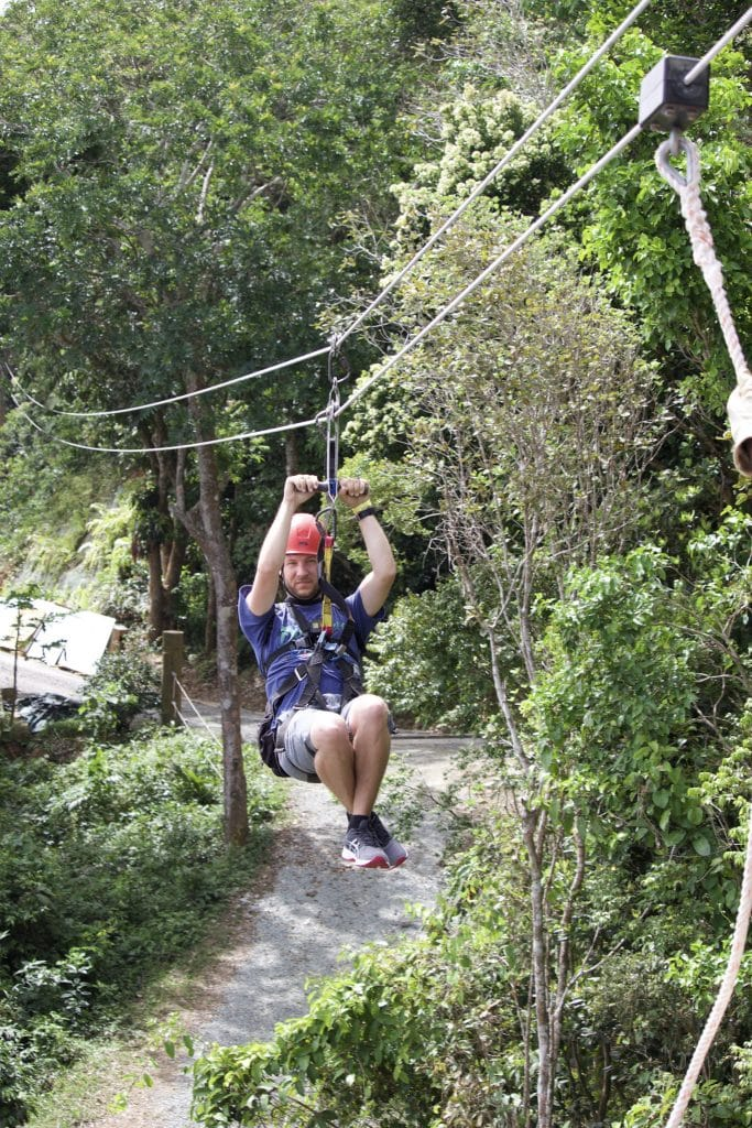 A man zip lining through the trees at Tree Limin Extreme in St. Thomas.