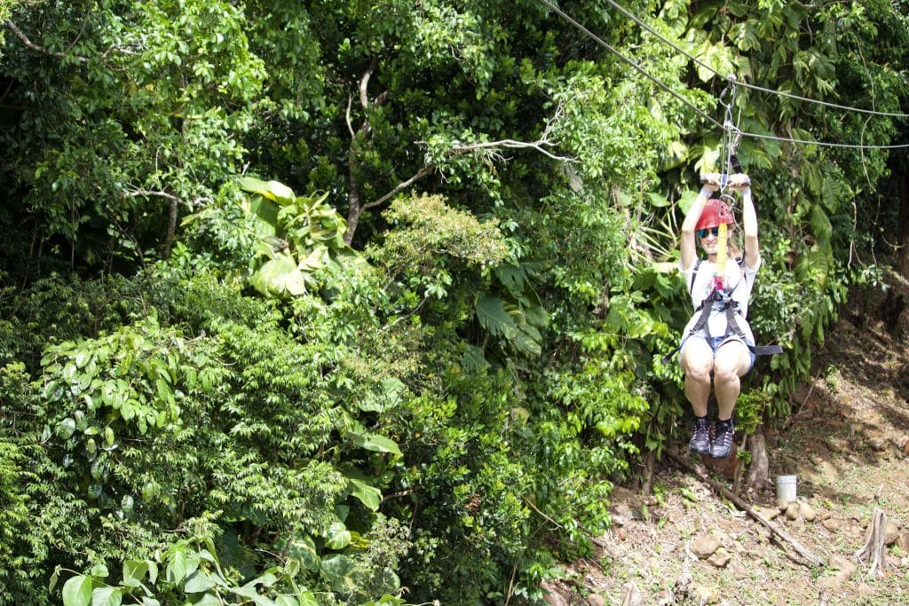 A young woman zip lining through the trees at Tree Limin Extreme in St. Thomas.