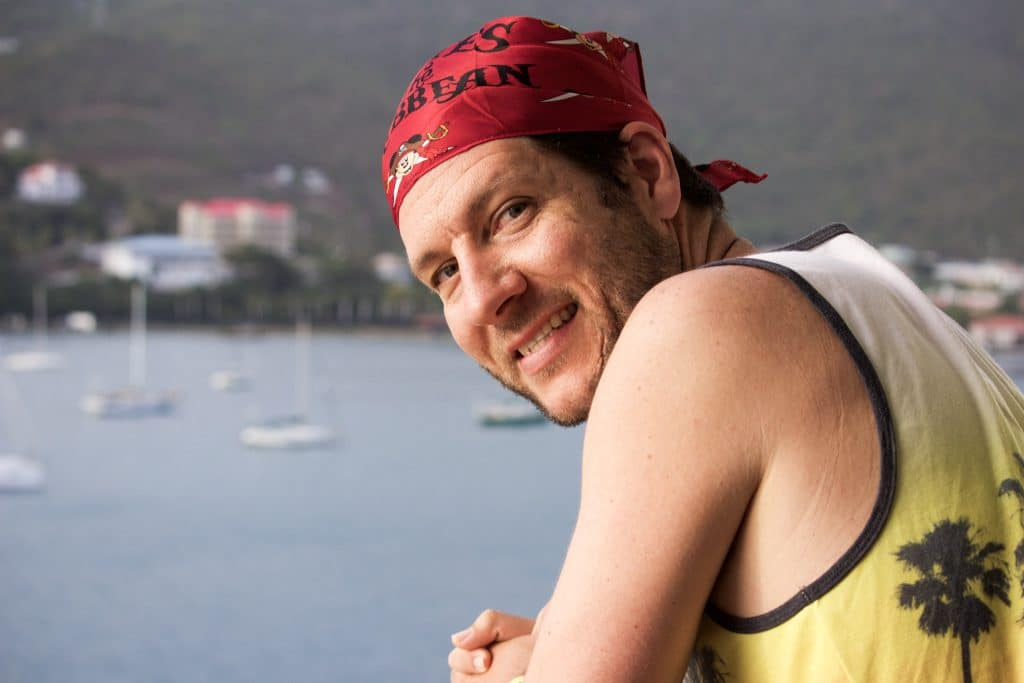 A man wearing a disney cruise pirate night bandana leaning over a railing by the water.