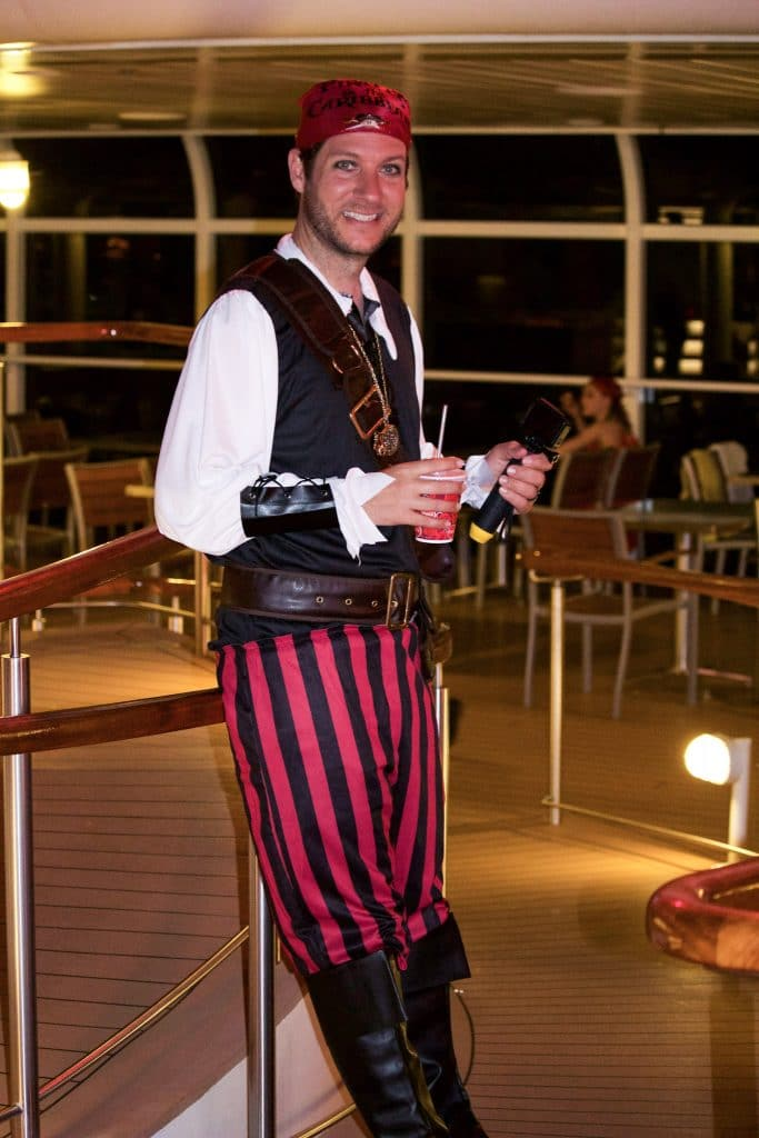 A man dressed in costume as a pirate holding a cup and leaning against a railing on a disney cruise ship.