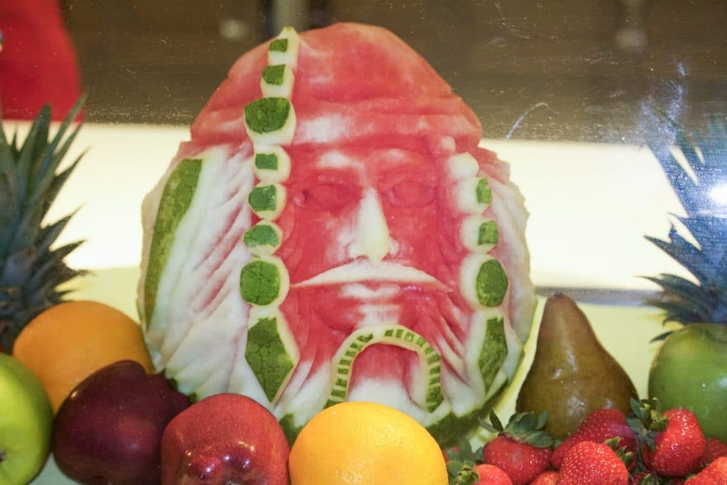 A watermelon is carved to look like Captain Jack Sparrow next to pieces of fruit.