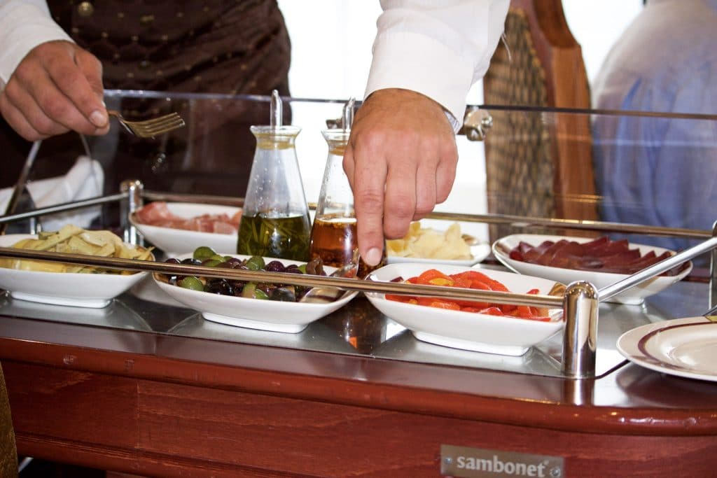 A man serving food from a charcuterie cart at Palo dinner.
