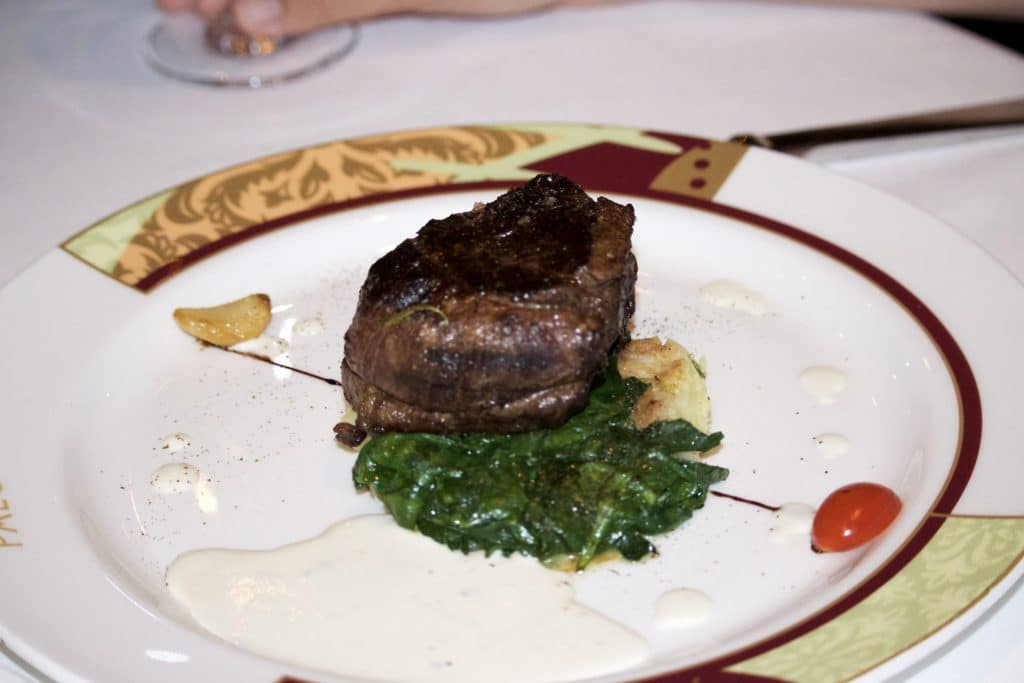 Beef tenderloin with blue cheese sauce on a bed of spinach on a plate at Palo for dinner.