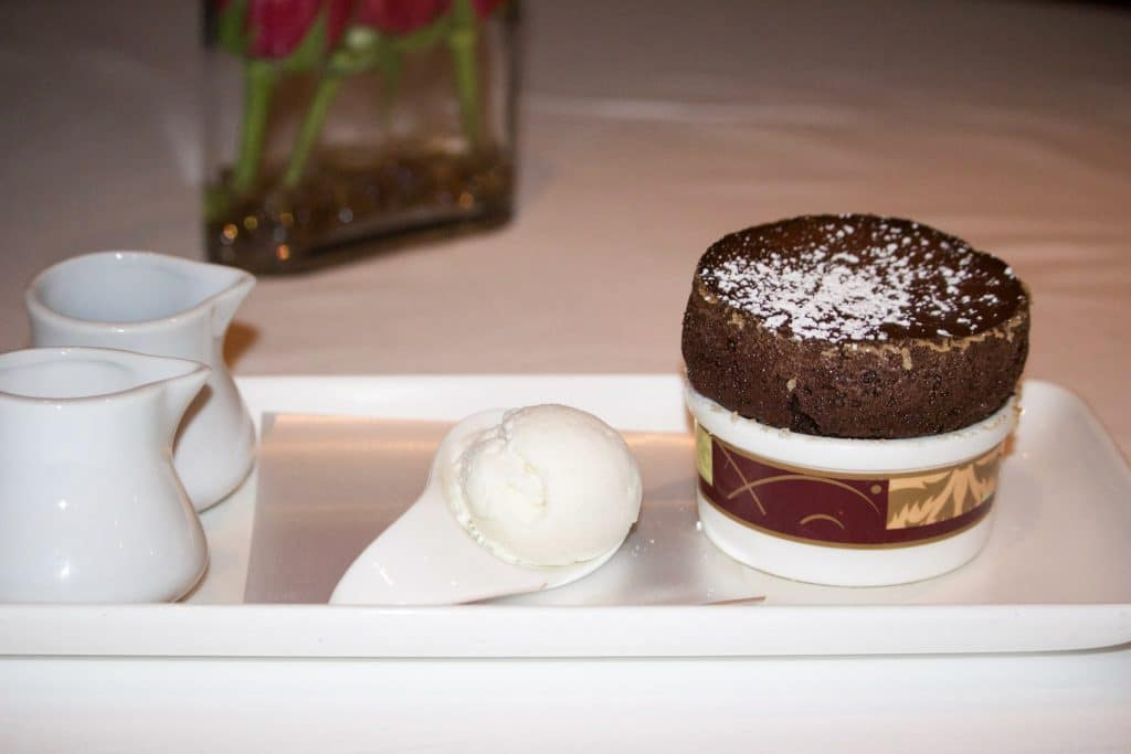 A chocolate souffle on a rectangular white plate with ice cream at Palo dinner.