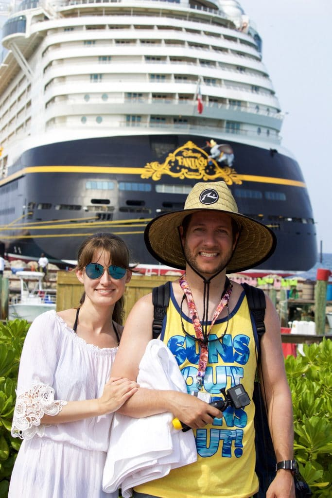 A man and a woman wearing beach gear and smiling in front of the Disney Fantasy at Castaway Cay.