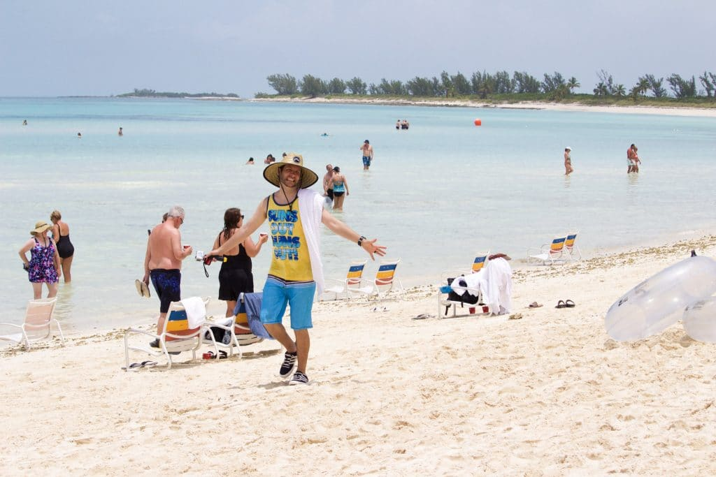 A man in a yellow tank top walking on the Serenity Bay beach at Castaway Cay.