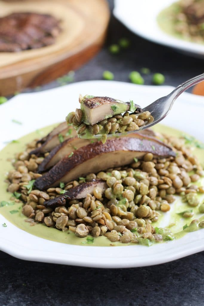 A fork holding a piece of portobello mushroom over a white plate filled with lentils and green sauce.