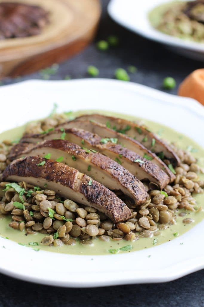 A sliced baked portobello mushroom on top of lentils and green sauce on a white plate.