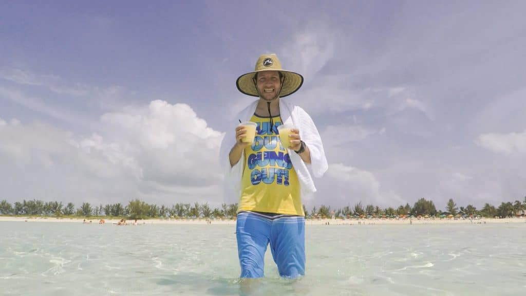 A man holding drinks while wading in shallow water in Serenity Bay at Castaway Cay.