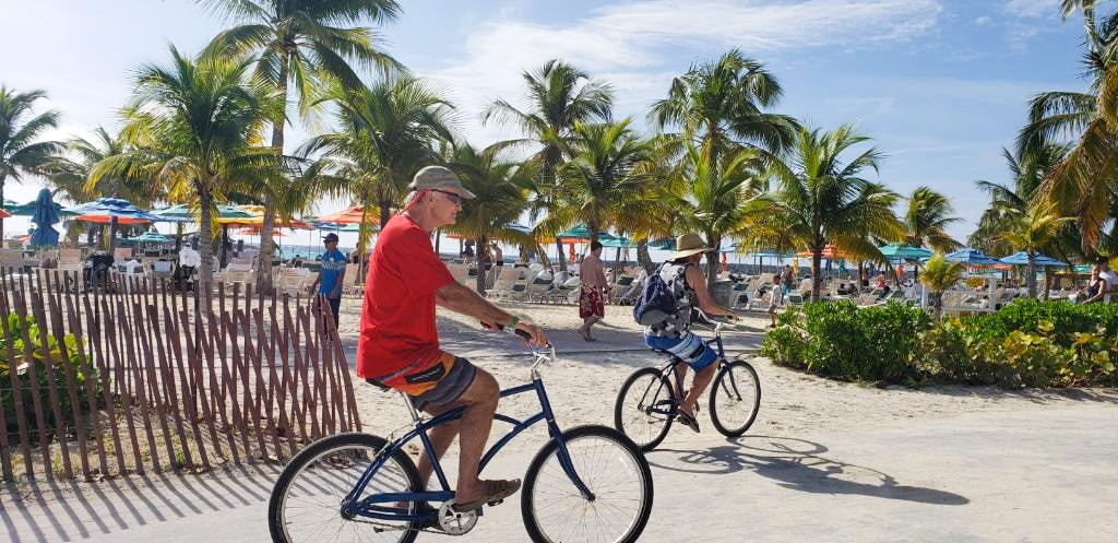 Two men riding bikes down the street on Castaway Cay.