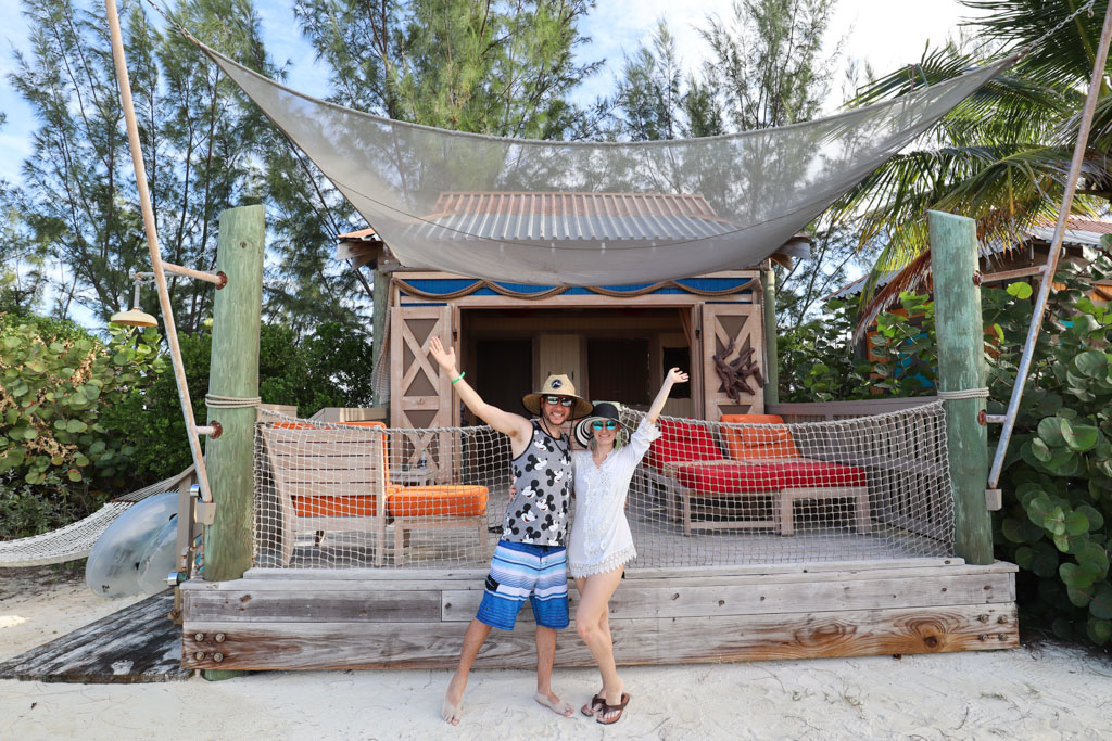 A happy couple standing in front of Cabana #24 in Serenity Bay at Castaway Cay.