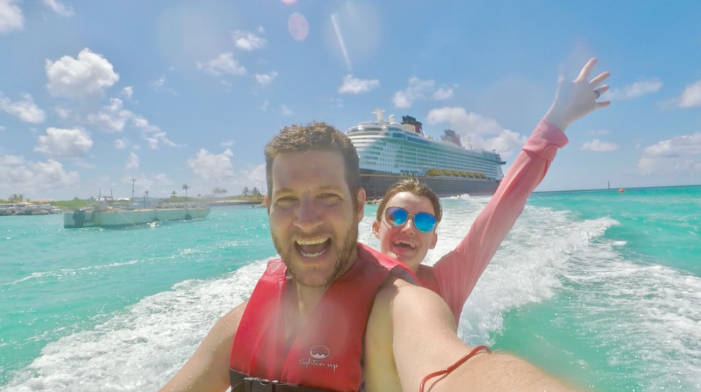 A happ couple riding a jet ski in the water in front of the Disney Fantasy on Castaway Cay.