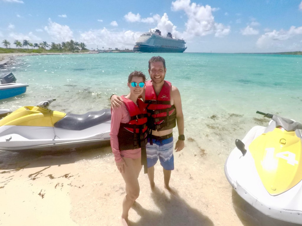 A happy couple standing on the beach next to jet skis in front of the Disney Fantasy on Castaway Cay.