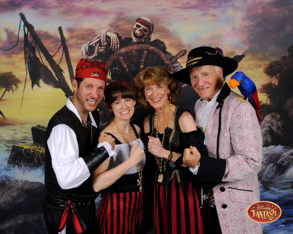 A family of four dressed like pirates in front of a pirate themed backdrop.