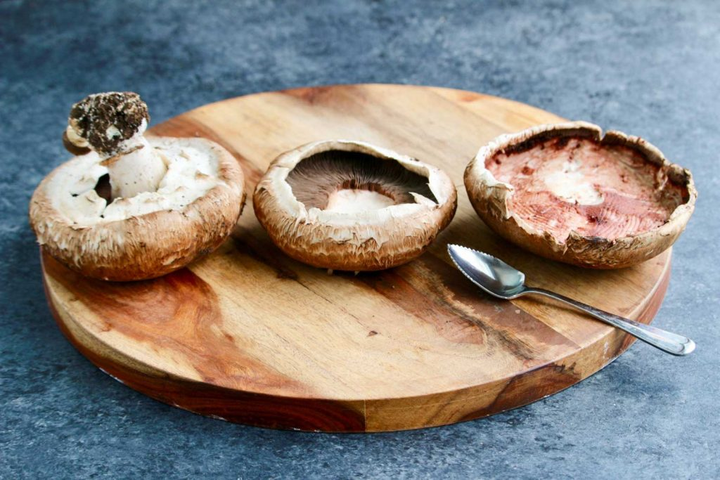 Three portobello mushrooms and a grapefruit spoon on a wooden board.