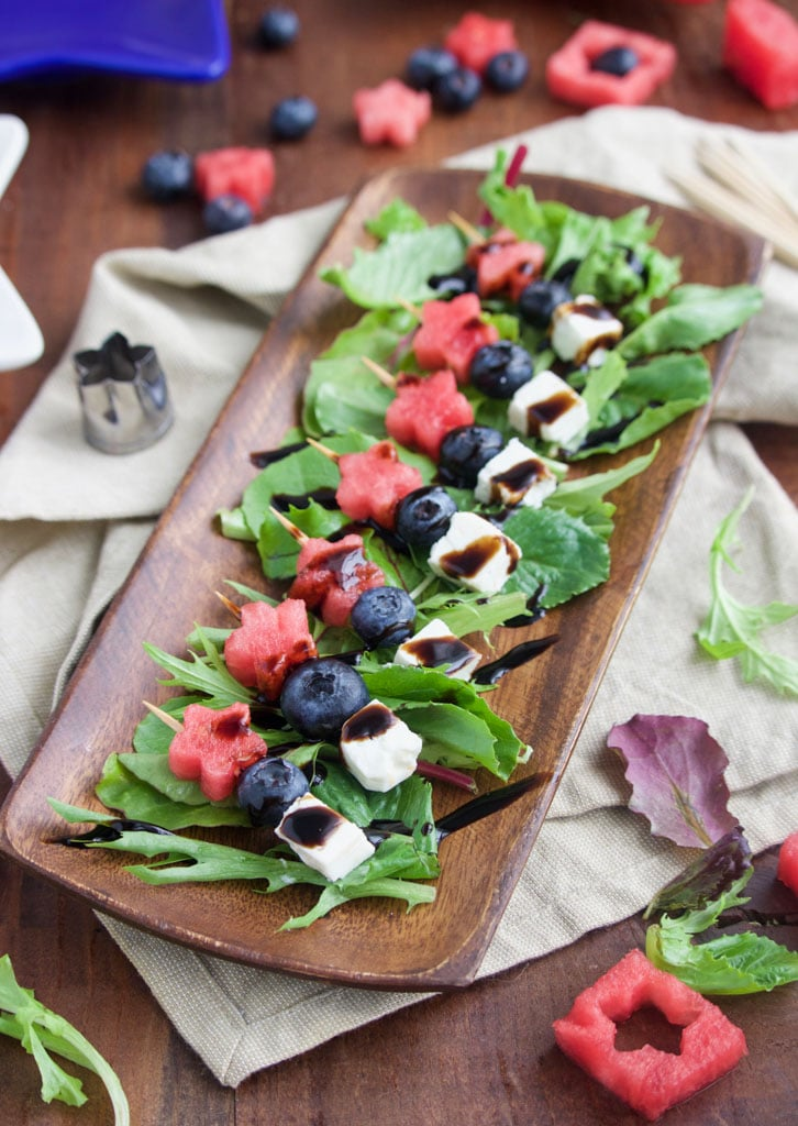 A platter of a red, white, and blue, vegan 4th of July appetizer skewers.