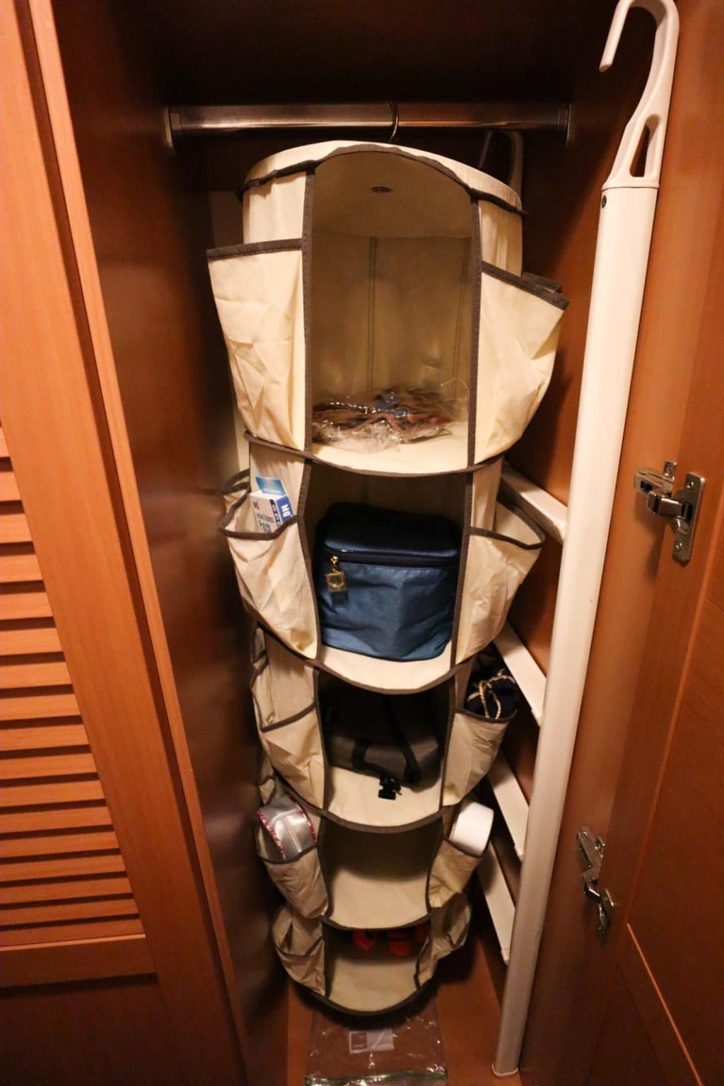 A spinning hanging organizer is hanging in the closet in a stateroom on the Disney Fantasy.