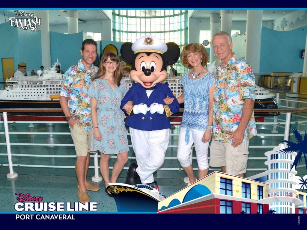 A family smiling and posing with Mickey Mouse at the Port Canaveral terminal.