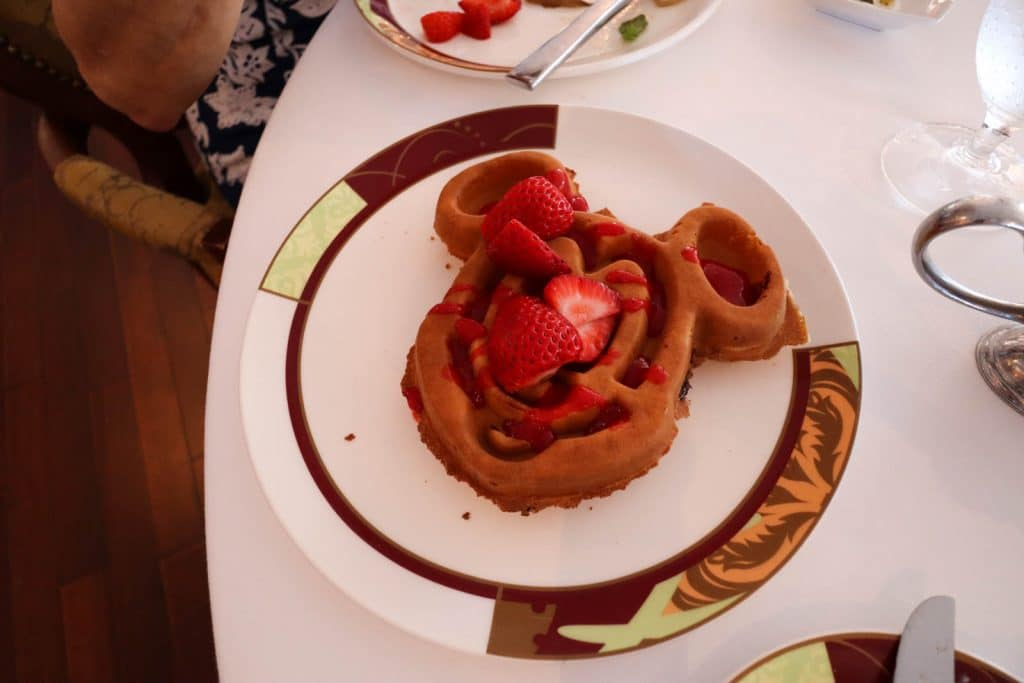 A giant Mickey waffle with strawberries on a table with a white table cloth at Palo brunch.
