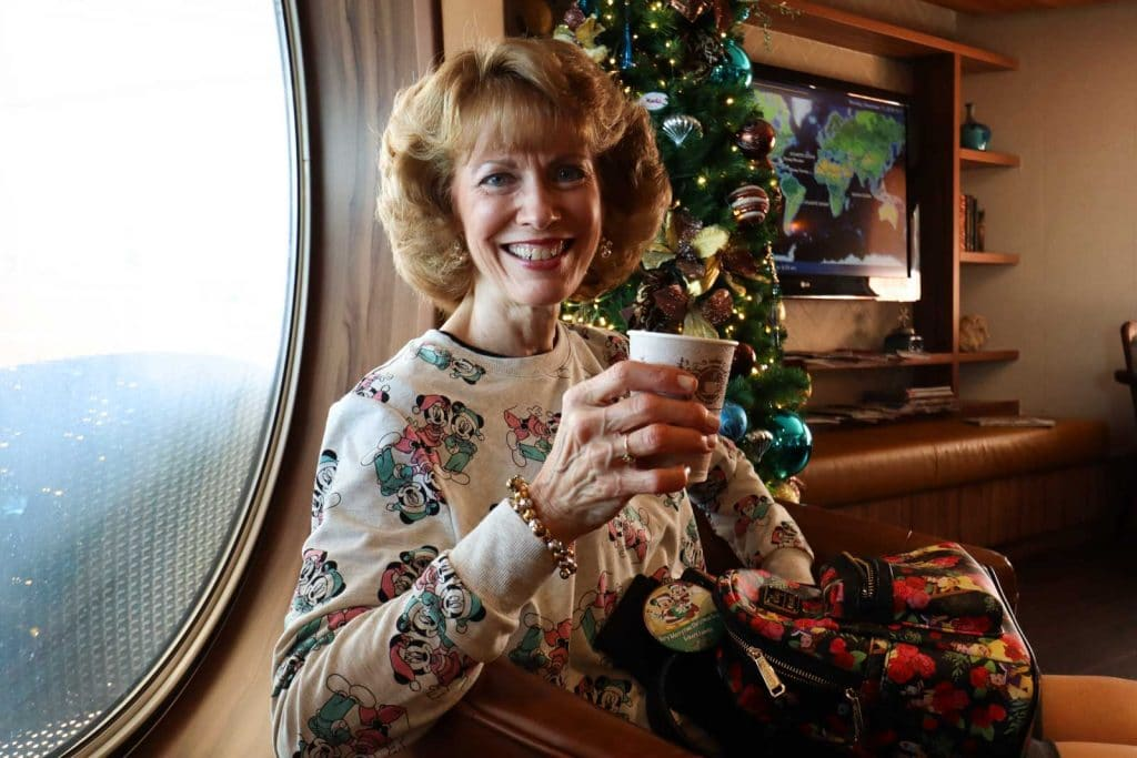 A woman holding a cup of coffee next t a christmas tree at Cove Cafe on the Disney Magic.