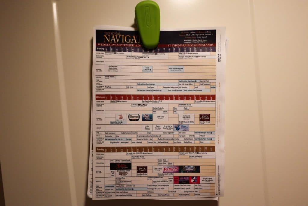 Disney cruise personal navigator's clipped and hanging on a door.