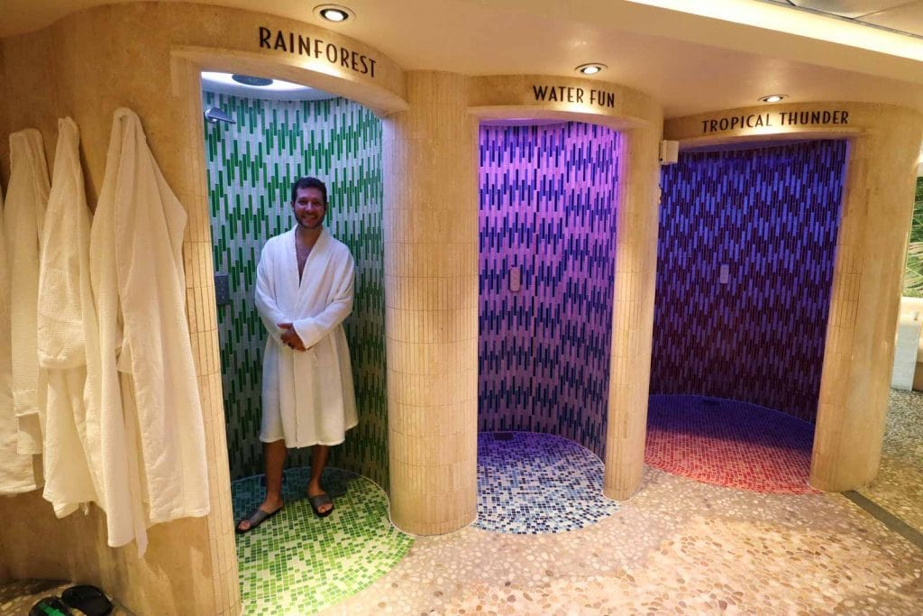 A man in a white bath robe standing inside the rainforest shower in senses spa on the Disney Fantasy.