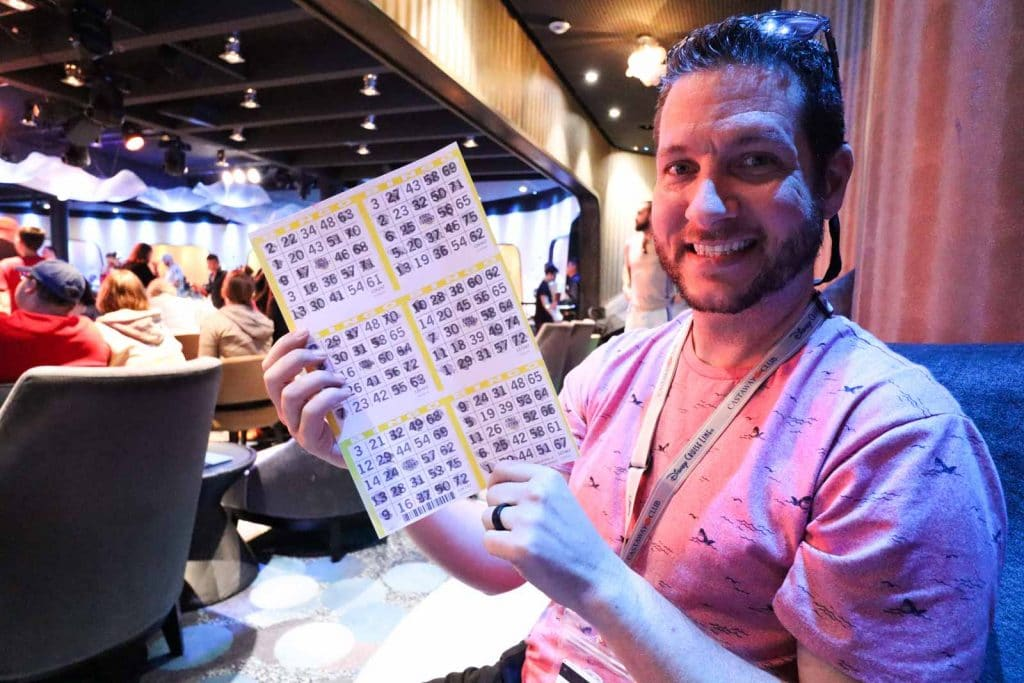 A man holding bingo cards after playing on bingo on a Disney cruise.