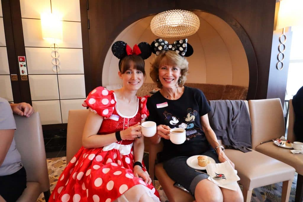 A mother and daughter dressed up for Halloween are holding coffee cups.